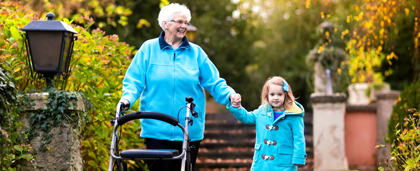 Elderly Woman Walking Hand-In-Hand With Small Child Outdoors