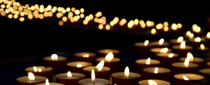Dozens Of Lit Candles Glowing In Darkness