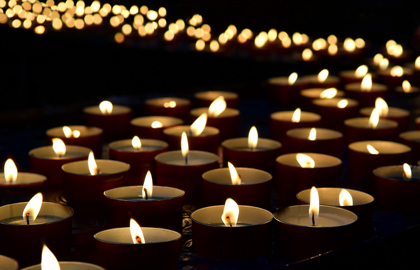 Lit Candles Glittering In Dark