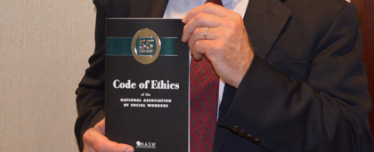 Man Holding Copy NASW Code Of Ethics